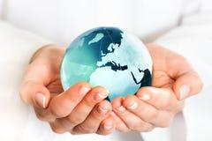 Ręka trzyma błękit ziemi kulę ziemską Obrazy Stock