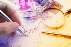 Ręka trzyma błękitnego ballpoint pióro analizuje techniczną mapę pieniężny instrument Zdjęcie Royalty Free