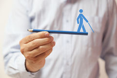 Ręka trzyma błękitnego ołówek z ludzką postacią na nim Obraz Stock