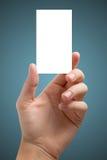 Ręka trzyma białą pustą biznesową wizyty kartę, prezent, bilet, przepustka, przedstawia odosobnionego na błękitnym tle Kopiuje pr Zdjęcia Stock