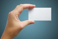 Ręka trzyma białą pustą biznesową wizyty kartę, prezent, bilet, przepustka, przedstawia odosobnionego na błękitnym tle Kopiuje pr Obraz Stock