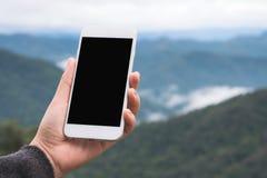 Ręka trzyma białego mądrze telefon z pustym desktop ekranem i pokazuje w plenerowym z plamy zieleni gór tłem obraz royalty free