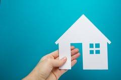 Ręka trzyma białego papieru domu postać na błękitnym tle koncepcja real nieruchomości target651_1_ ekologiczny Odbitkowy astronau Zdjęcia Stock