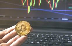Ręka trzyma Bitcoin monetę przed nowożytnym czarnym notatnikiem zakończenie fotografia Bitcoin, wekslowa wirtualna wartość zdjęcia stock