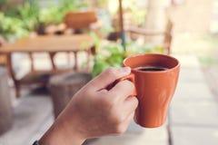 Ręka trzyma brown filiżankę gorąca kawa w ranku z plamy tłem Zdjęcie Stock
