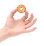 Ręka trzyma ciasto z białym kremowym sercem. Zdjęcie Stock