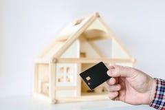 Ręka trzyma czarnego plastikowego układu scalonego keycard Drewniany domu model na tle Ochrona kędziorek Bezprzewodowy wejście ot zdjęcia stock