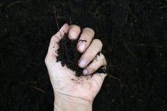 Ręka trzyma czerni ziemię Fotografia Royalty Free