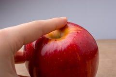 Ręka trzyma czerwonego jabłka na drewnie Zdjęcia Stock