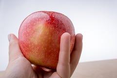 Ręka trzyma czerwonego jabłka na drewnie Obrazy Royalty Free