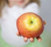 Ręka trzyma dojrzałego jabłka dziecko Zdjęcia Stock