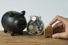 Ręka trzyma drewnianego miniatura dom z monetami w słoju i czerni Obraz Stock