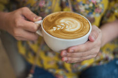 Ręka trzyma filiżankę latte kawa z kwiatu wzorem kobieta Fotografia Royalty Free