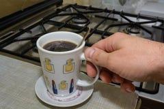 Ręka trzyma filiżankę natychmiastowa kawa pełno Obrazy Stock