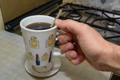 Ręka trzyma filiżankę natychmiastowa kawa pełno Obrazy Royalty Free