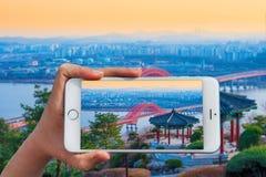 Ręka trzyma mądrze telefon bierze fotografię przy Banghwa mostem w Korea Obrazy Royalty Free
