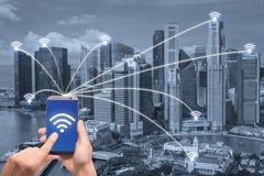 Ręka trzyma mądrze telefon i Singapur miasto z siecią łączymy Obrazy Royalty Free