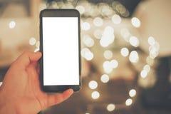Ręka trzyma mądrze telefon z pustym ekranem na tle chri Obrazy Stock