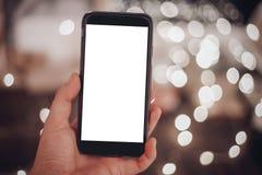 Ręka trzyma mądrze telefon z pustym ekranem na tle chri Obraz Royalty Free