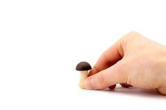 Ręka trzyma małej czekolady pieczarki na białym tle Obrazy Stock