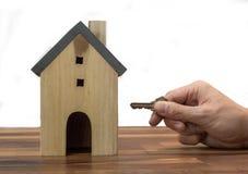 Ręka trzyma modela dom odizolowywający na białym tle i klucze, nieruchomość kupuje mieszkanie fotografia royalty free