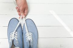 Ręka trzyma niebieskich dżinsów sneakers koronkami na białym drewnianym tle obrazy stock