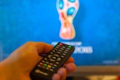Ręka trzyma pilot do tv TV przeciw zamazanemu ekranowi na którym transmituje futbol zdjęcia royalty free