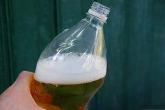 Ręka trzyma plastikową butelkę z żółtym napojem i biel pienimy się obraz royalty free