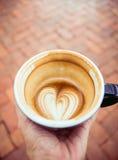 Ręka trzyma przyrodnią filiżankę gorąca dojna kawa w kierowym kształta latte ar Zdjęcie Stock