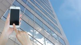 Ręka trzyma pustego ekranu mądrze telefon z buiding tłem Obrazy Stock