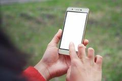 Ręka trzyma smartphone dla przedstawienia i dotyk z bielu ekranem jest plenerowy fotografia stock
