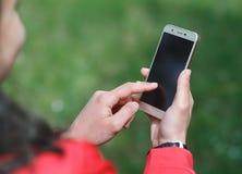 Ręka trzyma smartphone dla przedstawienia i dotyk z czerń ekranem jest plenerowy obraz royalty free