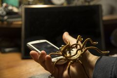 Ręka trzyma smartphone i pająk czołgać się nad nim, wirus, temat ewidencyjna ochrona obrazy stock