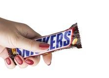 Ręka trzyma Snickers czekoladowego baru obraz royalty free