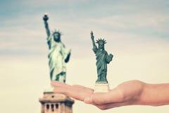 Ręka trzyma statuy wolności pamiątki zabawkę, istna statua wolności w tle Obrazy Stock