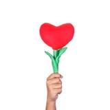 Ręka trzyma sztucznego czerwonego kierowego kwiatu Studio strzelający odosobniony o Zdjęcia Stock