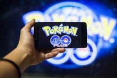 Ręka trzyma telefon komórkowego bawić się Pokemon Iść gra z plamy tłem Obrazy Royalty Free