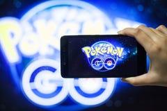 Ręka trzyma telefon komórkowego bawić się Pokemon Iść gra z plamy tłem Zdjęcia Stock