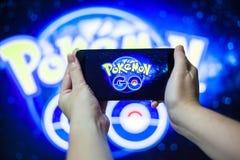 Ręka trzyma telefon komórkowego bawić się Pokemon Iść gra z plamy tłem fotografia royalty free