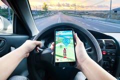Ręka trzyma telefon komórkowego bawić się Pokemon jadąca Iść gra podczas gdy zdjęcia stock