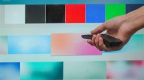 Ręka trzyma TV daleki na tle mądrze TV ekran zdjęcia stock