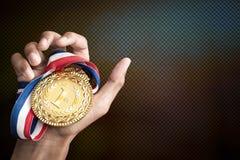Ręka trzyma up złotego medal Obraz Stock