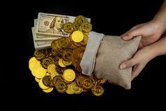 Ręka trzyma złocistą monetę w skarb sterty i worka plikach 100 USA dolarów banknotów fotografia royalty free