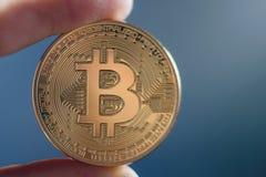 Ręka trzyma złotego Bitcoin wirtualnego pieniądze fotografia stock