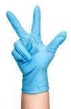 Ręka w błękitnej lateksowej rękawiczce pokazuje trzy palca pionowo Obrazy Royalty Free