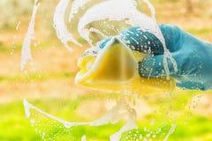 Ręka w gumowej rękawiczce myje okno Pojęcia sprzątanie, dom zdjęcia stock