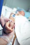 Ręka w rękawiczce trzymający ostrożnie pacjenta w ICU Obrazy Stock