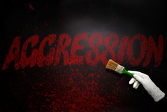Ręka w rękawiczce z szczotkarskim obrazem tekst agresja na b Fotografia Stock