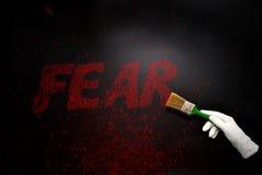 Ręka w rękawiczce z szczotkarskim obrazem teksta strach na czarnej powierzchni Fotografia Royalty Free