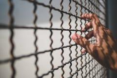 Ręka więźnia mienia metalu nieociosany ogrodzenie z deseniowym cieniem, przestępca blokował w więzieniu Zdjęcie Royalty Free
